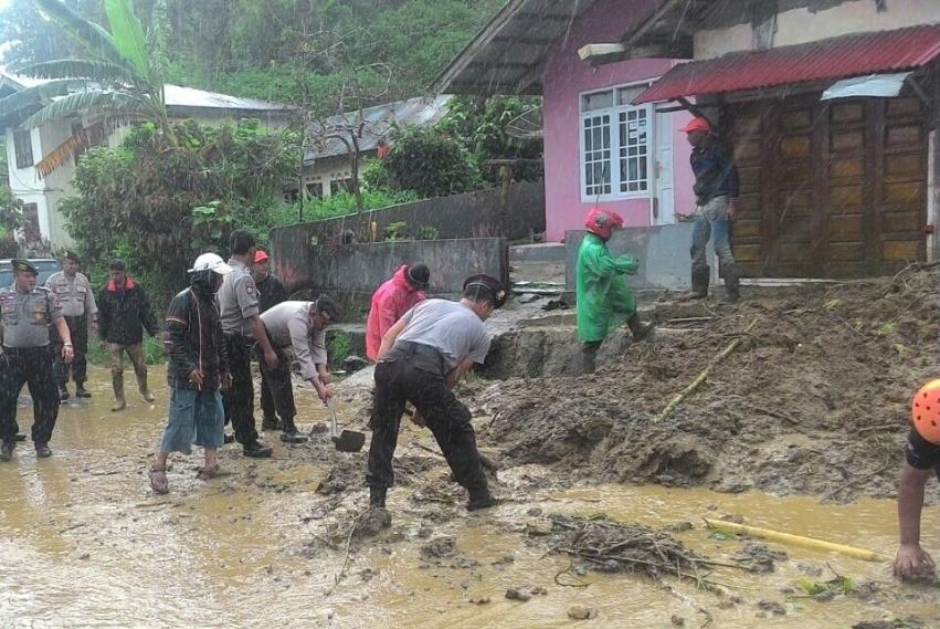 Angoota Polres Bukittinggi dengan masyarakat membersihkan material longsor dari rumah penduduk dan badan jalan